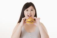 Young woman eating hamburger and smiling at the camera