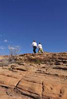 レイクパウエルの岩大地と歩く二人と青空