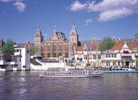 運河を移動する船と中央駅 オランダ