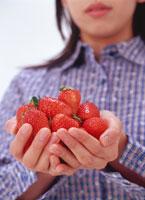山盛りのイチゴを持つ女性の手