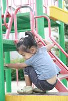 公園の遊具で遊ぶ女の子の後姿