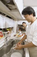 食器を洗う中年男性