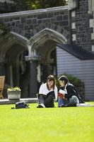 キャンパスの芝生に座る女性2人