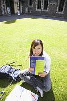 キャンパスの芝生に座る女性