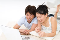 パソコンを見る20代のカップル