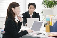 PC画面を眺めながら電話で会話する女性 11014005129| 写真素材・ストックフォト・画像・イラスト素材|アマナイメージズ