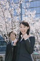 桜の花の前に立つスーツ姿の女性と男性