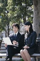 外のベンチで会話するスーツ姿の男性と女性