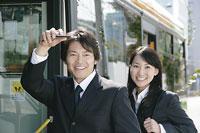 バスの前で人を呼ぶ男性と女性