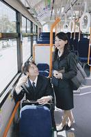 バスの中で会話をする男性と女性 11014005180| 写真素材・ストックフォト・画像・イラスト素材|アマナイメージズ