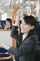 吊革につかまり時計を確認する女性 11014005189| 写真素材・ストックフォト・画像・イラスト素材|アマナイメージズ