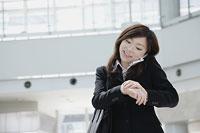 携帯電話で話しながら時間を確認する女性