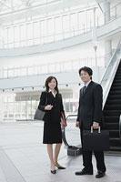 エスカレーターの前に立つ男性と女性