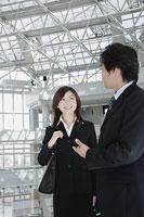 オフィスビルのロビーで男性と会話をする女性 11014005222| 写真素材・ストックフォト・画像・イラスト素材|アマナイメージズ