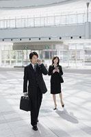 オフィスビルのロビーで携帯電話で話す男性と女性
