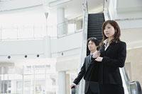 エスカレーターの前に立つ女性と男性 11014005229| 写真素材・ストックフォト・画像・イラスト素材|アマナイメージズ