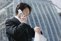 腕時計を見て携帯電話で話す男性