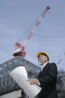 建築現場で図面を広げる男性
