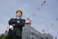 建築現場で腕組みをして立つ男性