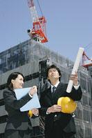 建築現場で会話をする男性と女性 11014005278| 写真素材・ストックフォト・画像・イラスト素材|アマナイメージズ
