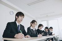 筆記試験を受けるスーツ姿の若い男女5人