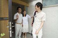 玄関で息子を見送る中年夫婦