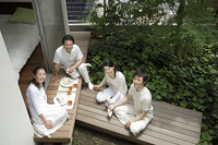 縁側で軽食を食べる中年夫婦と息子と娘