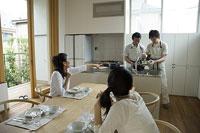 キッチンで料理をする父と息子を眺める母娘