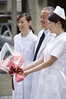花束を渡す看護師と医師