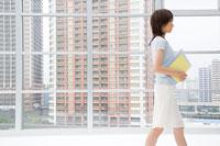 ファイルを持ってオフィスを歩く女性
