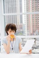 お茶を飲みながら書類に目をとおす女性