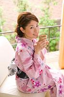 お茶を飲む浴衣姿の若い女性