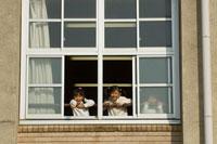校舎の窓から外を見る小学生