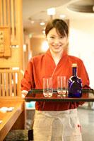 ボトルとグラスを運ぶ女性店員