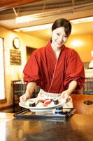 寿司を運ぶ女性店員