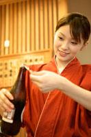 ビールの栓を開ける女性店員