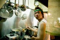 厨房で調理する店員