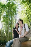 竹林の中のベンチに座る女性2人