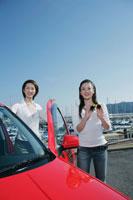ヨットハーバーで車から降りて立つ女性2人