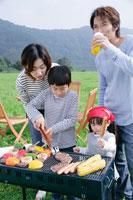 草原でバーベキューをする家族