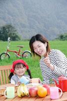 ピクニックテーブルに座る母と娘