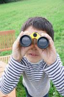 双眼鏡で遠くを見る男の子