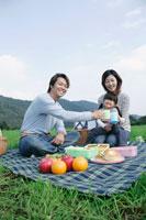 草原でピクニックをする親子3人