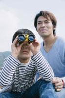 双眼鏡で遠くを見る父と息子
