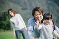 草原で自転車に乗る父と娘