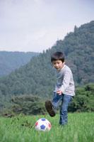 草原でサッカーボールを蹴る男の子