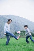 草原でサッカーをする父と息子