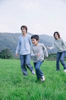 草原を走る親子3人
