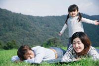 草原に寝そべる両親と娘