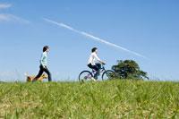 自転車で走る男性と犬を連れた女性